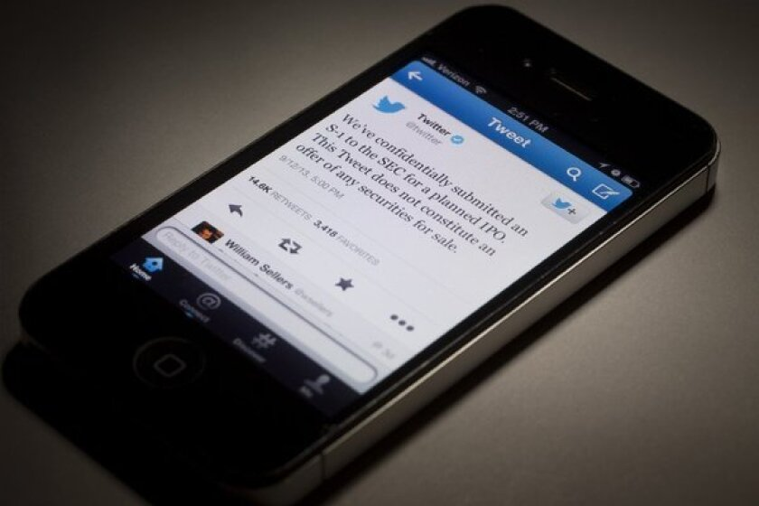 A tweet from Twitter on its upcoming IPO is displayed on a mobile device.
