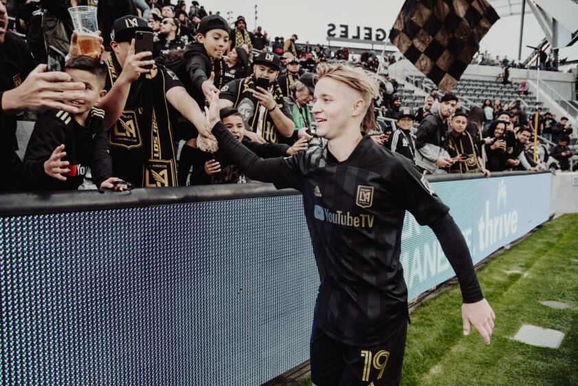 LAFC rookie midfielder Bryce Duke greets fans at a game.