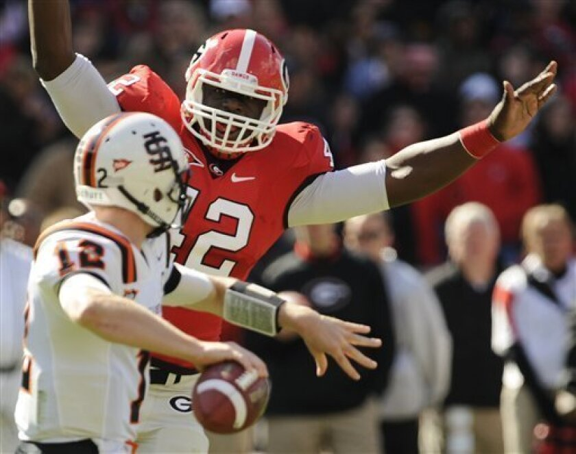 Georgia linebacker Justin Houston (42) pressures Idaho State quarterback Russel Hill (12) during the first half of an NCAA college football game Saturday, Nov. 6, 2010 in Athens, Ga. (AP Photo/Mike Stewart)