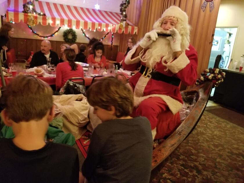 Santa John plays harmonica for children in the boat he made specifically to entertain them.