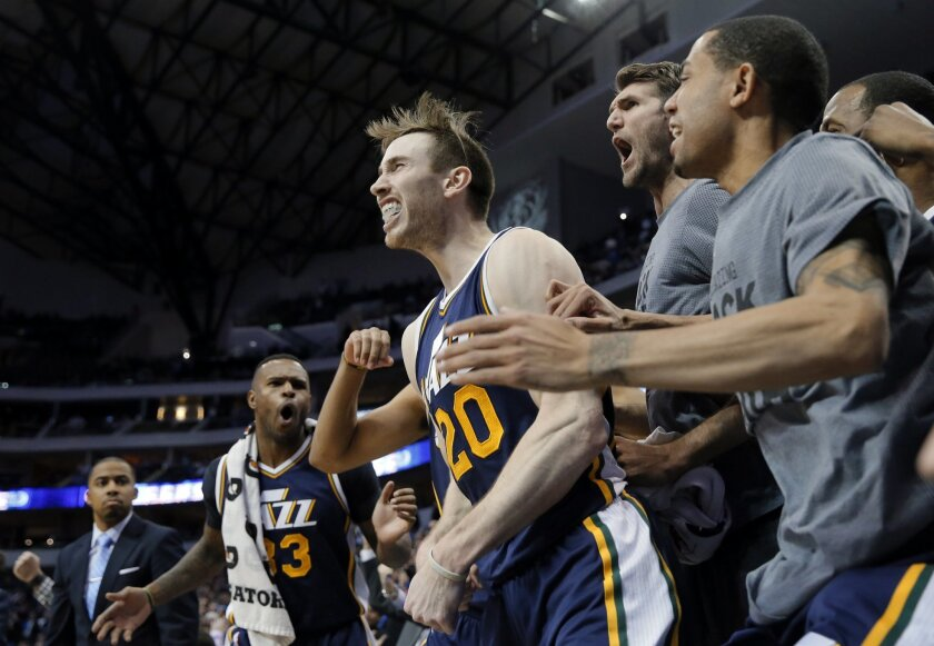 The Utah Jazz celebrate with Gordon Hayward (20) after Hayward sunk a basket at buzzer in overtime against the Dallas Mavericks in an NBA basketball game, Tuesday, Feb. 9, 2016, in Dallas. The Jazz won in 121-119. (AP Photo/Tony Gutierrez)