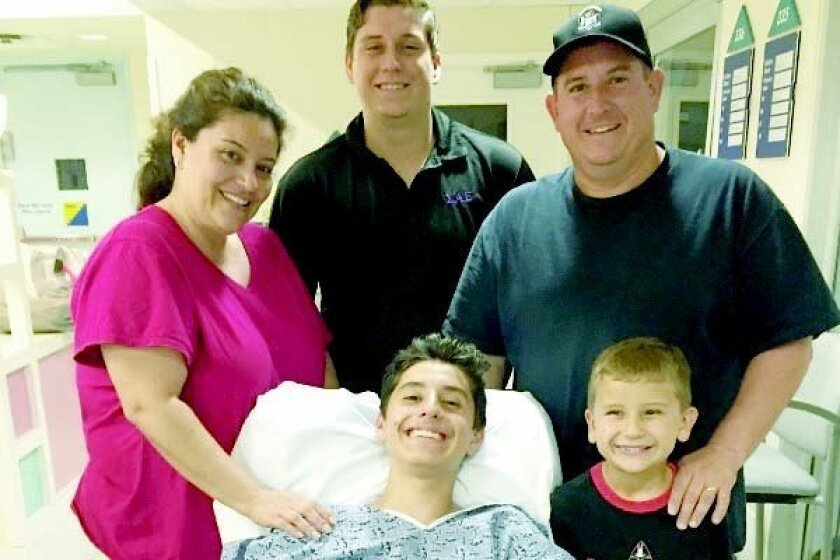 Danny Smuts Jr., center, with his family at a local hospital. CREDIT: Daniel Smuts