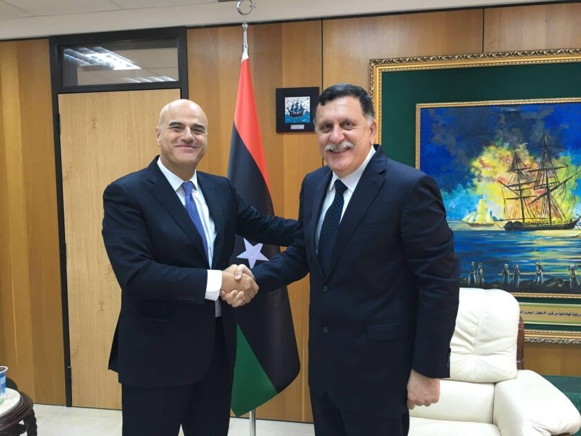 Italian oil giant Eni CEO Claudio Descalzi, left, and and Libya's new prime minister, Fayez al-Serraj shake hands in Tripoli, Libya, Saturday, June 4, 2016. The CEO of Italian oil giant Eni has traveled to Tripoli for the first time since July 2014 to meet with the new head of Libya's U.N.-backed g