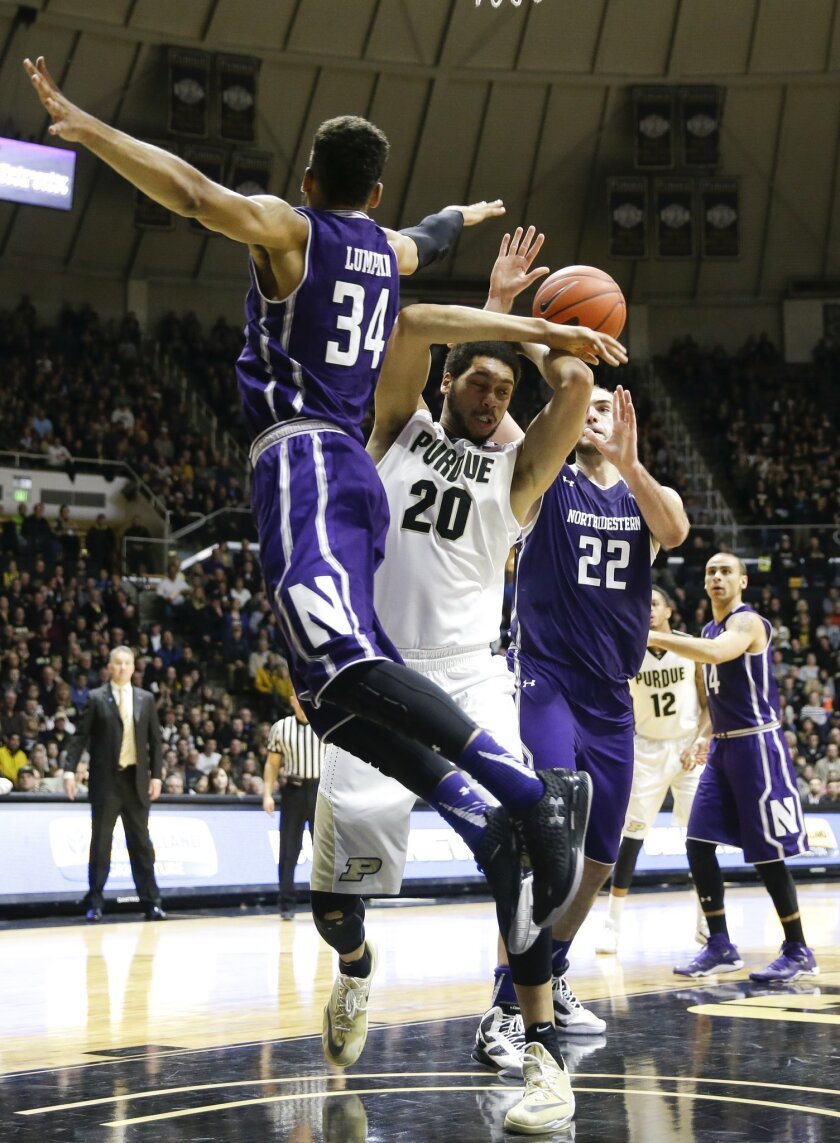 Purdue center A.J. Hammons (20) is fouled by Northwestern guard Sanjay Lumpkin (34) and center Alex Olah (22) in the second half of an NCAA college basketball game in West Lafayette, Ind., Tuesday, Feb. 16, 2016. Purdue defeated Northwestern 71-61. (AP Photo/Michael Conroy)