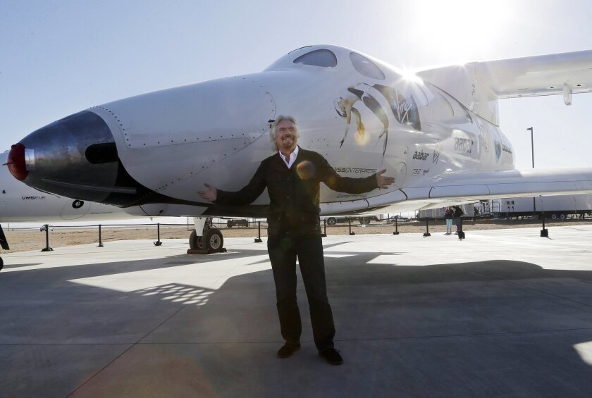 FILE - In this Sept. 25, 2013, file photo, British entrepreneur Richard Branson poses with the first SpaceShipTwo at a Virgin Galactic hangar at Mojave Air and Space Port in Mojave, Calif. Virgin Galactic will roll out a new copy of its space tourism rocket Friday, Feb. 19, 2016, as it prepares to resume flight testing for the first time since a 2014 accident destroyed the original and killed one of its two pilots. (AP Photo/Reed Saxon, File)