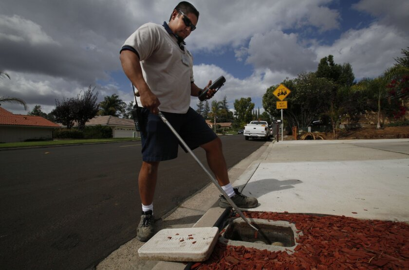 Public works employee Tim Carrillo demonstrates reading a meter in north Poway. Peggy Peattie • U-T
