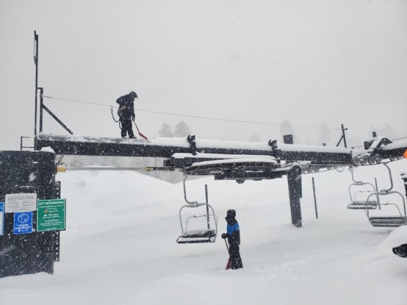 Workers clear snow from a ski lift at Snow Valley Mountain Resort after a storm dumped roughly a foot of powder in the area on Sunday.