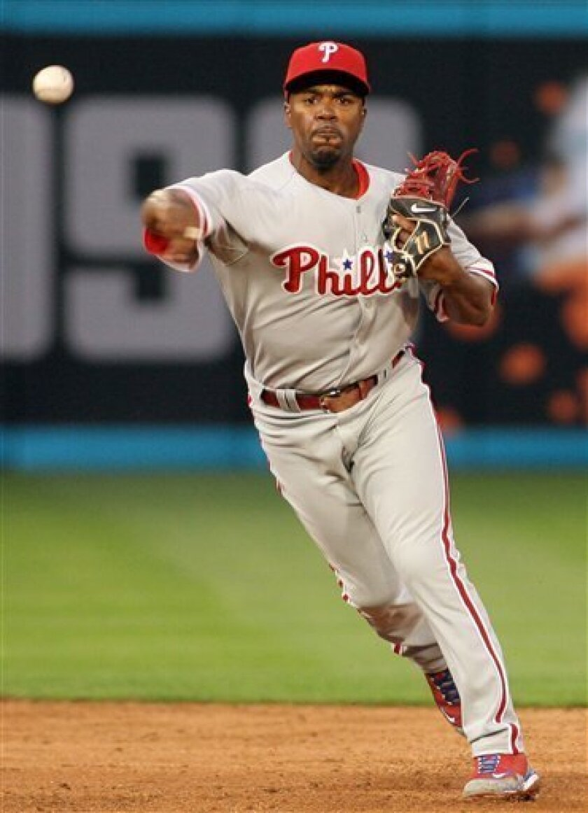 Philadelphia Phillies' Jimmy Rollins throws out Florida Marlins' Logan Baker during the second inning of a baseball game in Miami, Fla., Friday, April 24, 2009. (AP Photo/Jeffrey M. Boan)