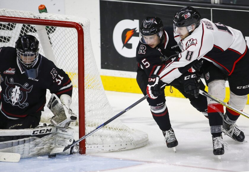 Rouyn-Noranda Huskies' Anthony-John Greer, right, tries to get the puck past Red Deer Rebels goalie Rylan Toth, left, as Josh Mahura defends during the second period of a semifinal in the CHL Memorial Cup hockey tournament, Friday, May 27, 2016, in Red Deer, Alberta. (Jeff McIntosh/The Canadian Pre