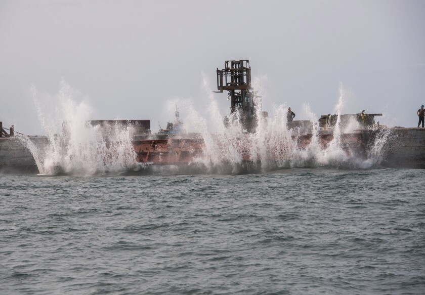 In this photo provided the Office of Governor Andrew M. Cuomo, an old rail car is dumped into the ocean a few miles off shore from Point Lookout, N.Y., Wednesday, Sept. 16, 2020. The debris will be used to create an artificial reef that will attract fish and other marine life. (Darren McGee/Office of Governor Andrew M. Cuomo via AP)