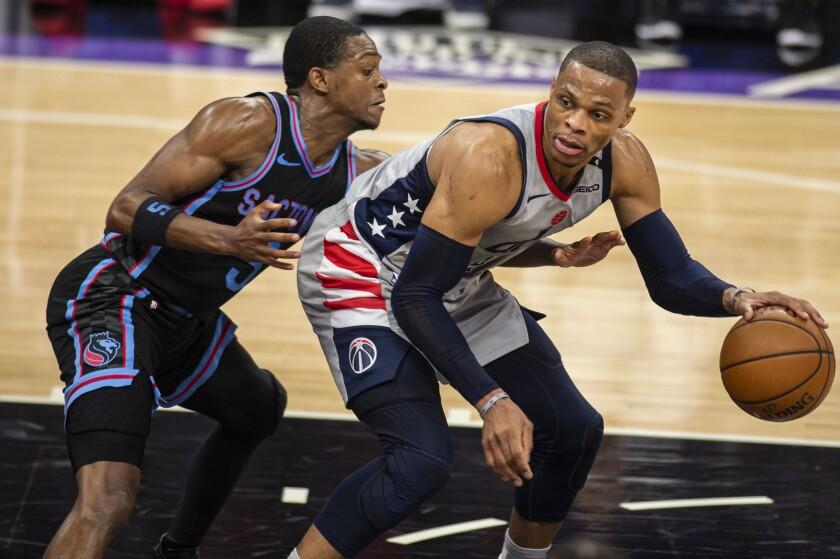 El jugador de los Kings de Sacramento De'Aaron Fox (5) defiende a su rival de los Wizards de Washington Russell Westbrook (4) mientras intenta jugar la pelota en el segundo cuarto del juego de la NBA que enfrentó a ambos equipos, en Sacramento, California, el 14 de abril de 2021. (AP Foto/Hector Amezcua)