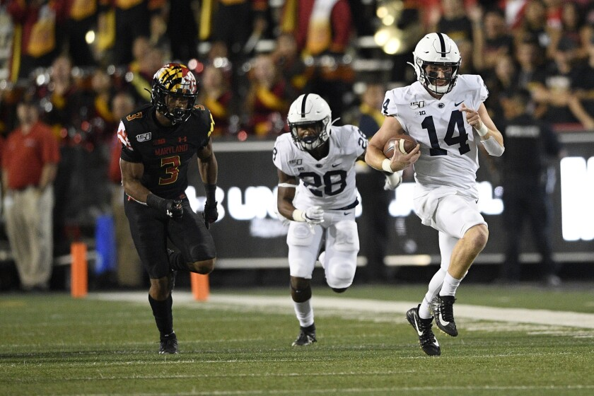 Penn State quarterback Sean Clifford (14) scrambles with the ball against Maryland defensive back Nick Cross (3) during the first half on Friday in College Park, Md.