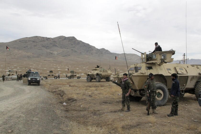 Troops and armored military vehicles next to a dirt road