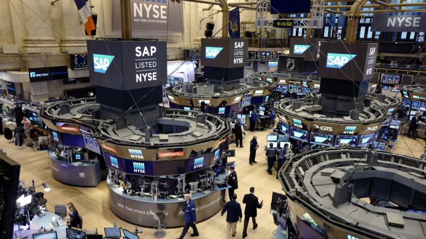 FILE- In this Feb. 9, 2017, file photo, traders work the floor at the New York Stock Exchange. The U