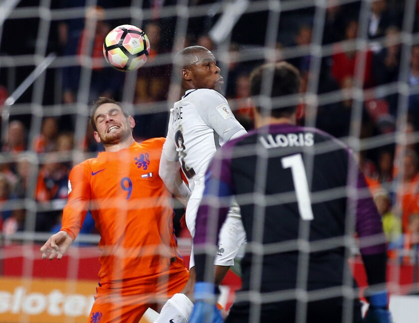 Netherlands' Vincent Janssen, left, heads the ball with France's Djibril Sidibe, center, while France's goalkeeper Hugo Lloris looks on during the World Cup Group A qualifying soccer match in the ArenA stadium in Amsterdam, Netherlands, Monday, Oct. 10, 2016. France defeated Netherlands 1-0. (AP Photo/Peter Dejong)