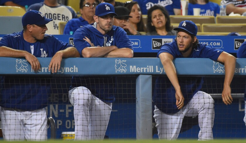 Dodgers ace Clayton Kershaw, right, chatting with catcher A.J. Ellis, left, and pitcher Brandon McCarthy, might not pitch again this season.