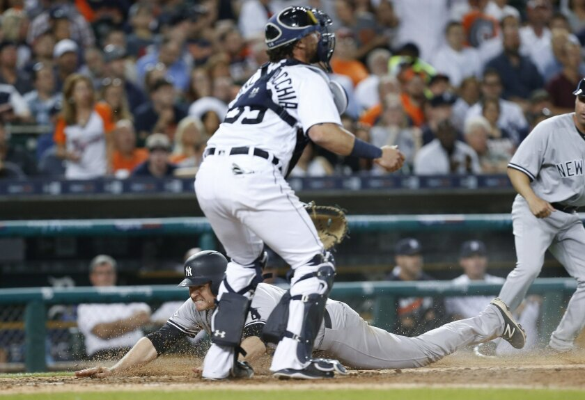 New York Yankees' Chase Headley dives safely into home plate as Detroit Tigers catcher Jarrod Saltalamacchia waits for the throw on a Robert Refsnyder single during the seventh inning of a baseball game in Detroit, Thursday, June 2, 2016. (AP Photo/Paul Sancya)