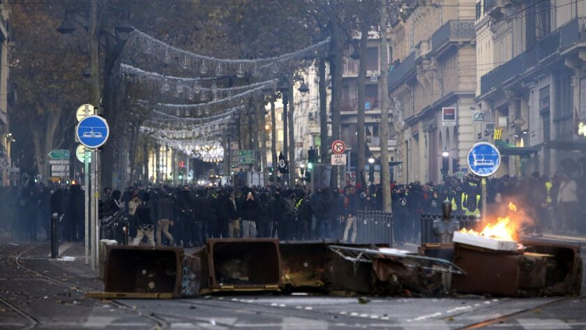 Demonstrators stand behind a burning bin during clashes, Saturday, Dec. 8, 2018 in Marseille, southe