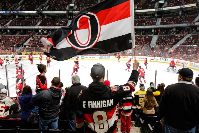 An Ottawa Senators fan waves a team flag before a game against the Boston Bruins on March 10.