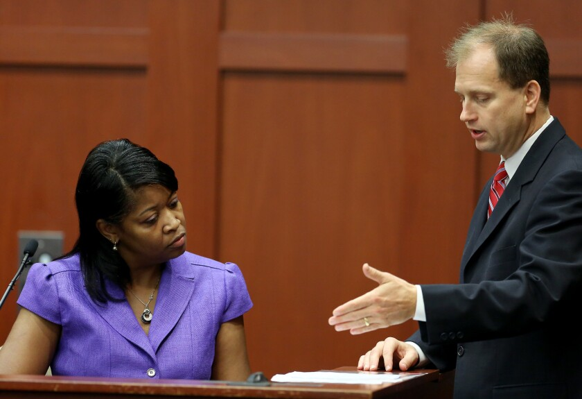 Sonja Boles-Melvin, registrar for Seminole State College, looks at a document presented by Assistant State Attorney Richard Mantei, during the George Zimmerman trial in Seminole County circuit court, in Sanford, Fla.