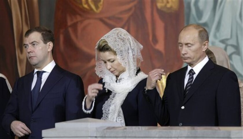 Russian President Dmitry Medvedev, left, his wife Svetlana, center, and Prime Minister Vladimir Putin cross themselves during the enthronement service for Patriarch Kirill, in Moscow's Christ the Saviour Cathedral, Sunday, Feb. 1, 2009. The new patriarch was seated on the throne of the Russian Orthodox Church Sunday, becoming the first leader of the world's largest Orthodox church to take office after the fall of the Soviet Union. (AP Photo/Misha Japaridze)