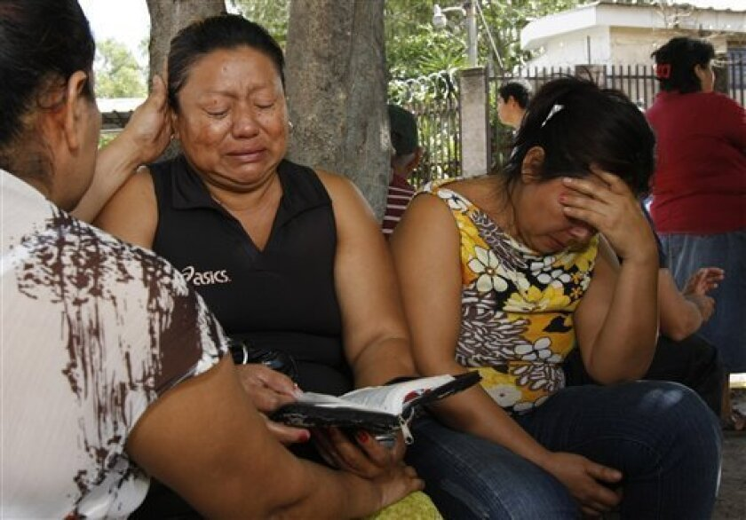 Zuleyma Martinez, center, reacts as she waits for the remains of her son outside the morgue in San Salvador, Monday, June 21, 2010. Martinez's son was killed during an attack to a public bus Sunday night in the northern area of San Salvador, killing at least 10 people who were aboard and leaving se