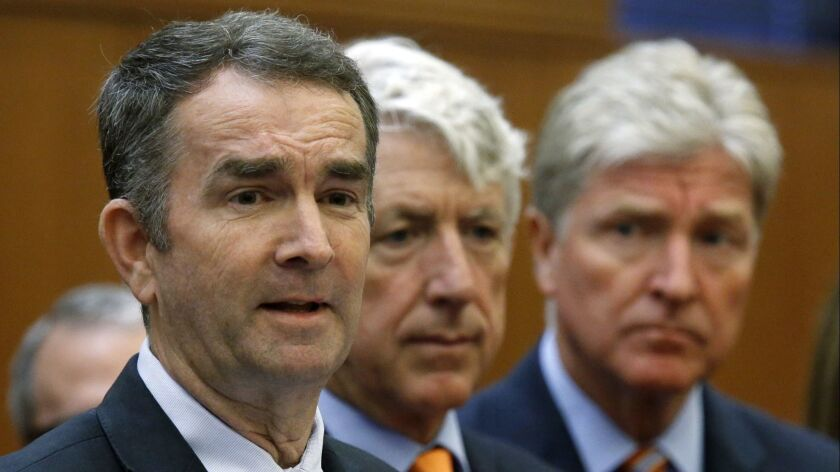 Virginia Gov. Ralph Northam, left, makes remarks at a press conference dealing with gun violence whi