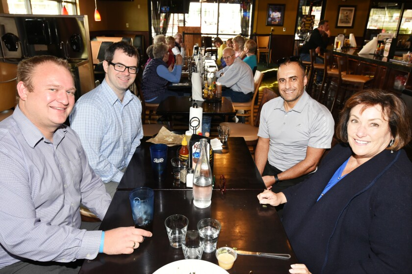 North San Diego Business Chamber members Andrew Stocker, Neil McCarthy, Areian Kouros and Debra Rosen eating lunch at Kaminski's Sports Lounge and Barbecue on Monday.