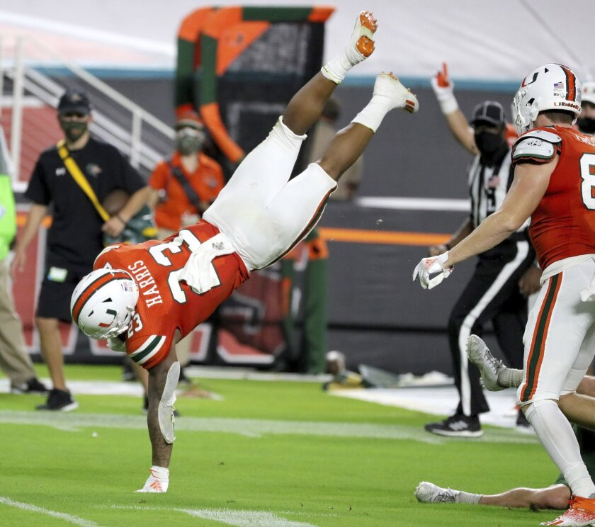 Miami running back Cam'Ron Harris (23) cartwheels over a UAB defender in the third quarter during an NCAA college football game in Miami Gardens, Fla., Thursday, Sept. 10, 2020. (Al Diaz/Miami Herald via AP)
