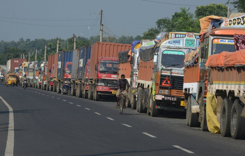 An Indian man cycles past parked Indian trucks carrying goods to Nepal near the India-Nepal border at Panitanki on Tuesday.