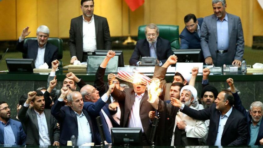 Members of Iran's parliament burn a U.S. flag in Tehran on Wednesday.