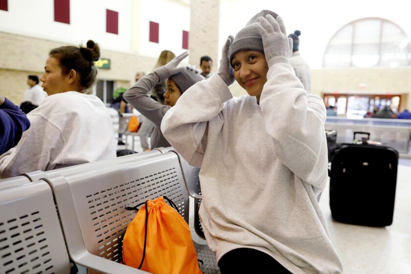 Ruth Avila, 19, of Quetzaltenango, Guatemala, tries on a donated beanie after being released from immigration detention in Brownsville.