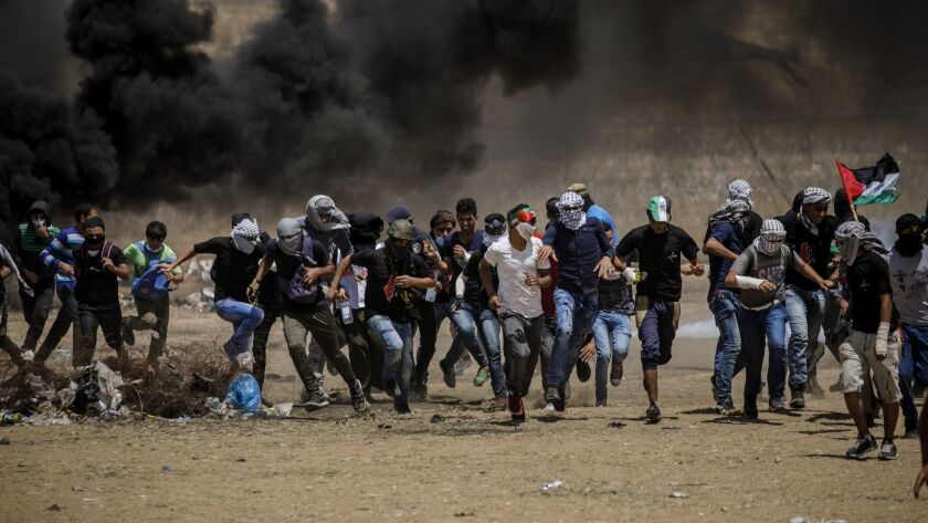 KHAN YOUNIS, GAZA STRIP -- FRIDAY, MAY 11, 2018: Palestinian protesters run away from tear gas duri