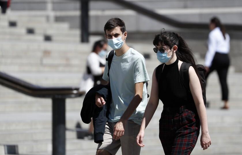 Dos personas caminan por la Plaza Trafalgar el jueves 30 de julio de 2020 portando mascarillas