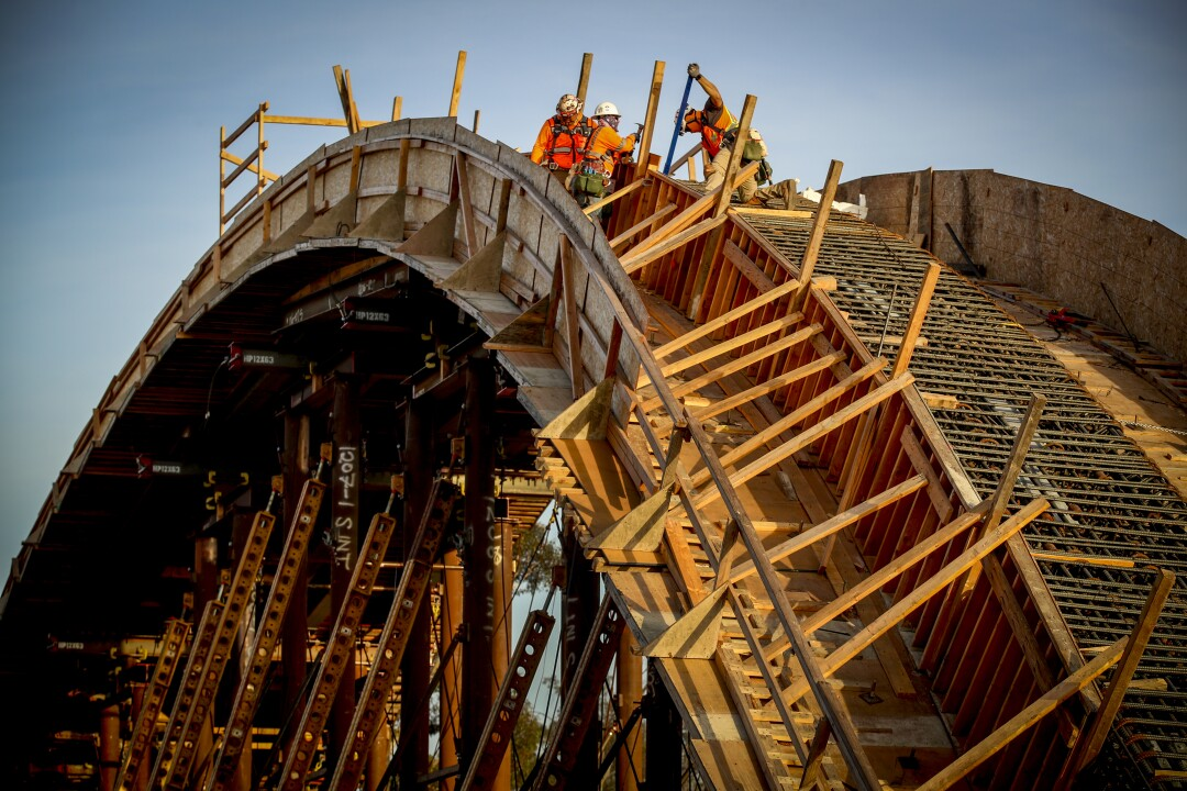 Workers build wooden framework on one arch