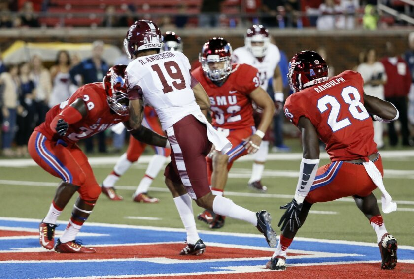 Temple wide receiver Robby Anderson (19) lands in the end zone after catching a pass for a touchdown between SMU defenders defensive back Darrion Richardson (29) and defensive back Shakiel Randolph (28) in the first half of an NCAA college football game Friday, Nov. 6, 2015, in Dallas. (AP Photo/To