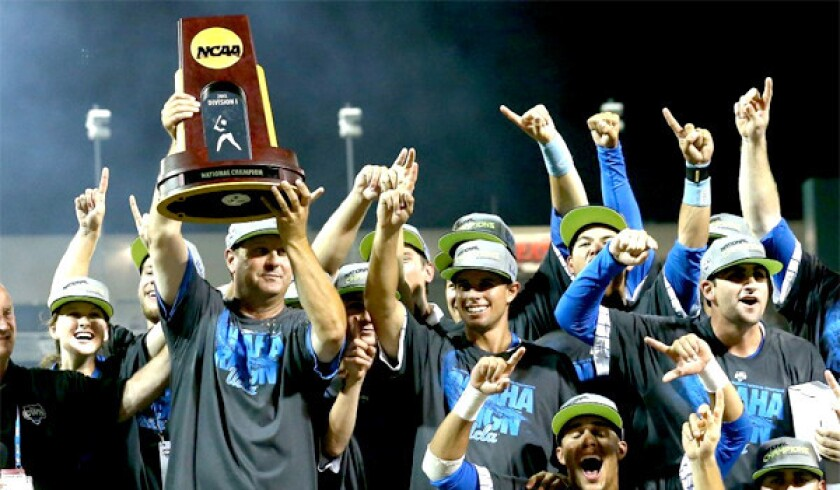 UCLA coach John Savage holds the championship trophy after beating Mississippi State to win the College World Series in 2013.