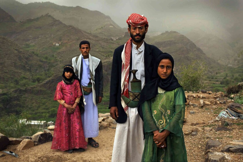 Stephanie Sinclair's documentation of child, early and forced marriage, part of an exhibit titled Women Look Out, at the Arena1 Gallery in Santa Monica, includes a portrait of two young girls, Tahani, left, and her friend Ghada, with their much older husbands in Hajjah, Yemen.