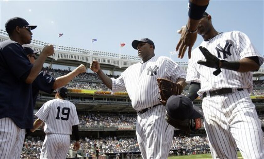 New York Yankees' CC Sabathia, center, leaves the field during the seventh inning of the baseball game against the Milwaukee Brewers, Thursday, June 30, 2011, at Yankee Stadium in New York. Sabathia allowed no runs and struck out 13 batters until he was taken out of the game in the eighth inning. (