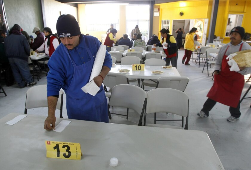 Julio Figueroa, deported last year from San Diego, set tables before meal service last month at the Desayunador Padre Chava in Tijuana.