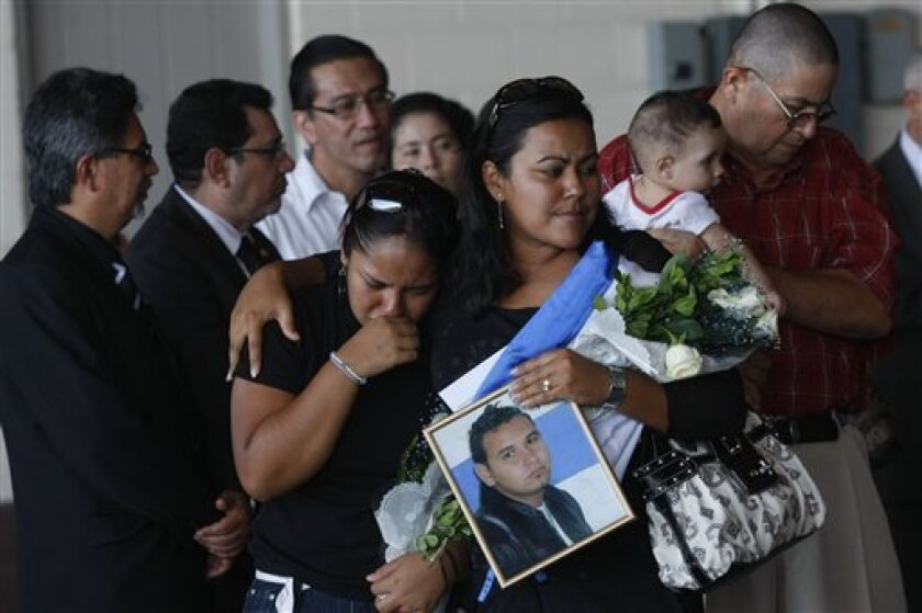 Relatives of Armando Nieto carry his photograph at a ceremony where people retrieved the bodies of relatives who were killed in Mexico, at a military base in Comalapa, El Salvador, Sunday Sept. 5, 2010. Nieto is one of 72 migrants who were killed, allegedly by the Zetas drug gang, in August in northern Mexico while trying to reach the U.S. border. (AP Photo/Edgar Romero)