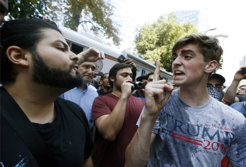 """A man wearing a T-shirt bearing the name of President Donald Trump, right, argues with a counter-protester after being hit by a plastic bottle of water near a """"free speech"""" rally staged by conservative activists."""