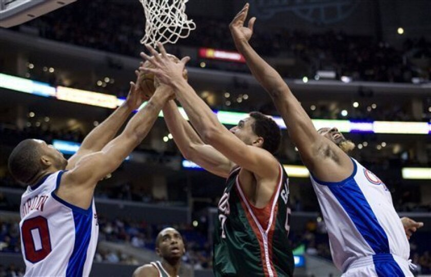 Milwaukee Bucks' Dan Gadzuric, center, fights for a rebound with Los Angeles Clippers' Eric Gordon, left, and Brian Skinner during the first quarter of an NBA basketball game in Los Angeles on Saturday, Jan. 17, 2009. (AP Photo/Hector Mata)