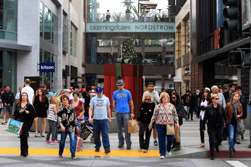 Black Friday shoppers cross the street in Santa Monica. Stores have seen a drop-off in business after a successful Black Friday weekend.