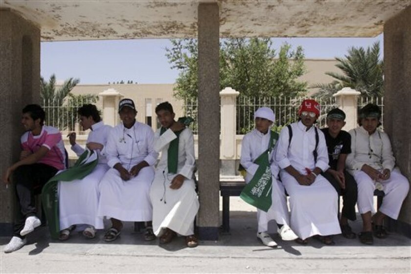 FILE - In this THursday, April 28, 2011 file photo, schoolboys display Saudi flags and headbands thanking Saudi King Abdullah while sitting at a bus stop in Hamad Town, Bahrain, west of the capital of Manama, Bahrain. After four months of Shiite-led protests and harsh crackdowns, Saudi Arabia has become the protector, patron and political gatekeeper for Bahrain's Sunni monarchy in the Gulf leadership's front-line fight against the Arab Spring.(AP Photo/Hasan Jamali, File)