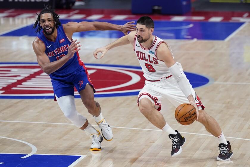 El pivot de los Bulls de Chicago Nikola Vucevic avanza hacia la canasta mientras lo defiende el pivot de los Pistons de Detroit Jahlil Okafor en el encuentro del domingo 9 de mayo del 2021. (AP Photo/Carlos Osorio)