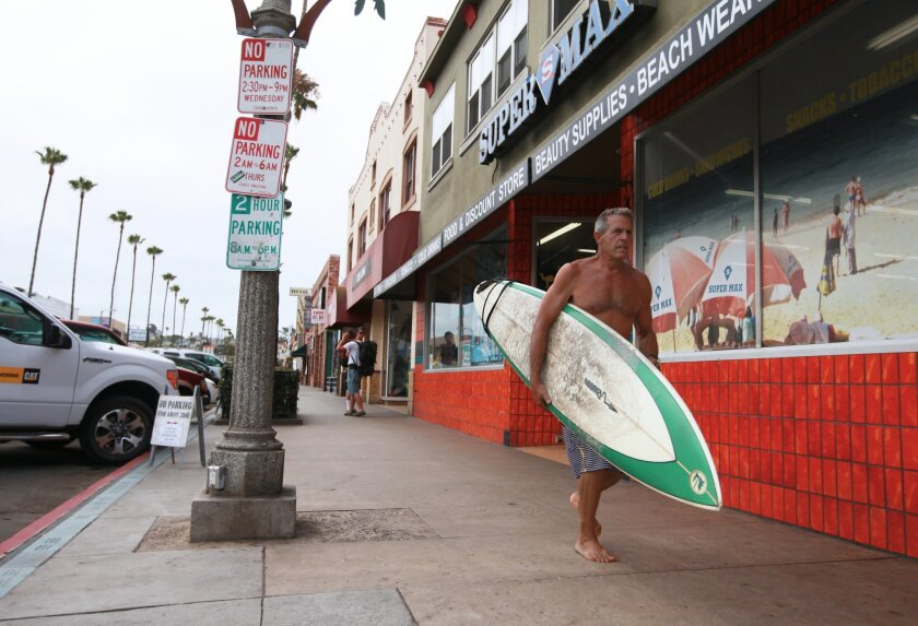 June, 27, 2014. Surfer and OB resident Michael Flentie jogs down Newport to get into the water for some decent waves.  Mandatory Credit U-T Photo Christian Rodas