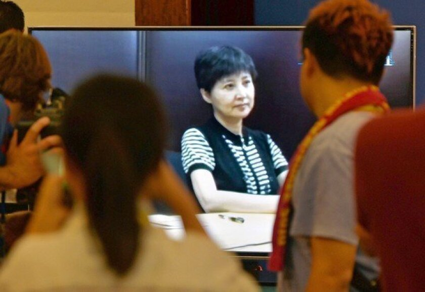 Journalists watch Gu Kailai, center, as her recorded testimony is presented during the corruption trial of her husband, Bo Xilai, in court in Jinan, China.