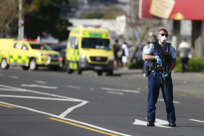 A police officer stands on a street with a rifle