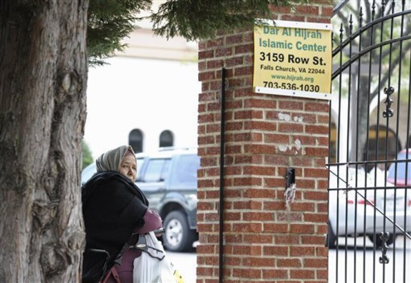 A woman waits at the gates of the Dar Al Hijrah Islamic Center in Falls Church, Va., Friday, Sept. 30, 2011. U.S. air strikes in Yemen on Friday killed Anwar al-Awlaki, an American militant cleric at the mosque, who became a prominent figure in the terror network's most dangerous branch, using his fluent English and Internet savvy to draw recruits for attacks in the United States. (AP Photo/Cliff Owen)